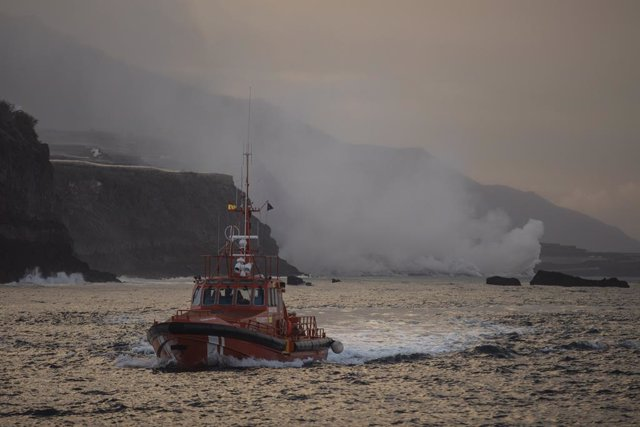 Un barco navega cerca de la columna de humo y la lava del volcán de Cumbre Vieja a su llegada al Océano Atlántico, a 29 de septiembre de 2021, en La Palma, Santa Cruz de Tenerife, Islas Canarias, (España). La lava del volcán, que entró el 19 de septiembre
