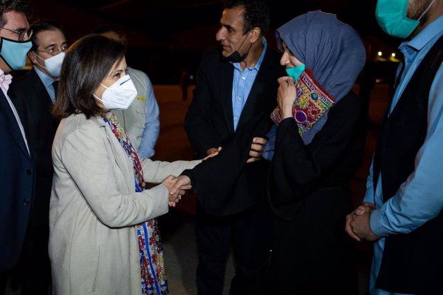 Margarita Robles saluda a los afganos que han llegado este lunes a la base aérea de Torrejón, en Madrid
