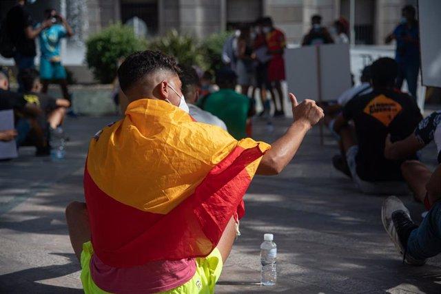 Archivo - Un joven durante una concentración en apoyo a las personas migrantes, organizada por las asociaciones No Name Kitchen y Maakun, en la plaza de los Reyes, a 17 de julio de 2021, en Ceuta (España).