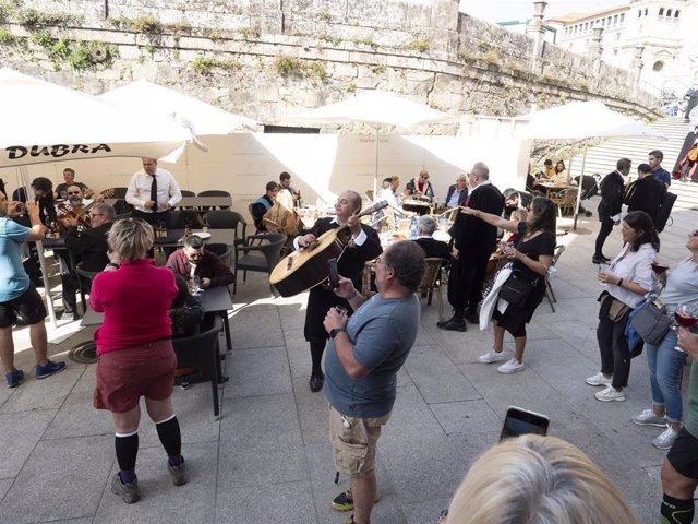 Un grupo de turistas canta con una tuna en una plaza de Santiago de Compostela, a 9 de octubre de 2021.