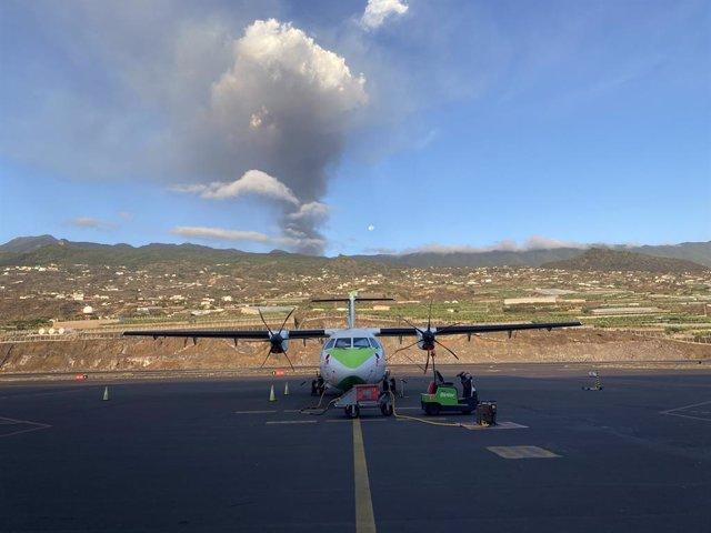 Un avión de Binter en la pista del aeropuerto de La Palma, con el volcán en erupción al fondo