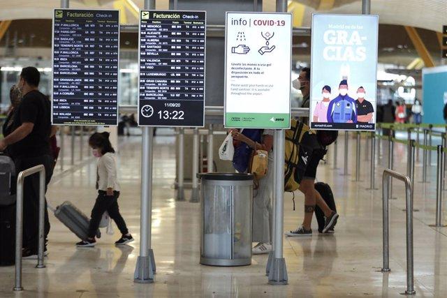 Archivo - Pasajeros cerca de páneles informativos en la terminal T4 del aeropuerto Adolfo Suárez Madrid-Barajas.