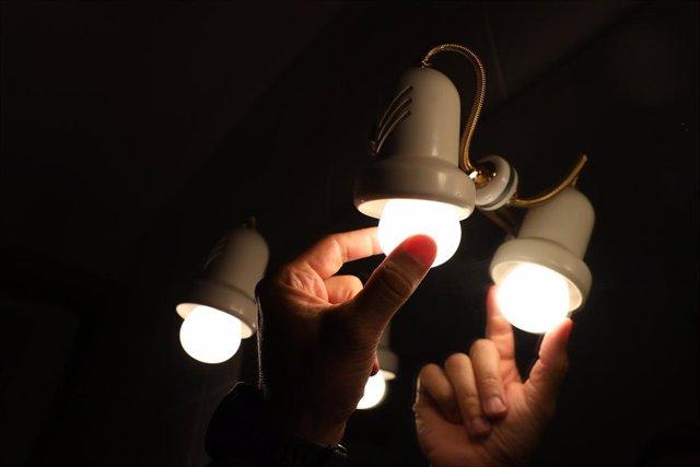Archivo - Una persona cambia la bombilla de una lámpara