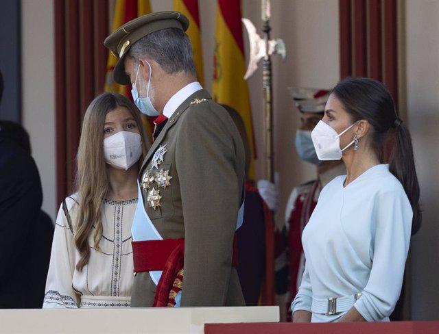 La infanta Sofía habla con su padre el rey Felipe VI, al lado de la reina Letizia, durante el acto solemne de homenaje a la bandera nacional y desfile militar en el Día de la Hispanidad, a 12 de octubre de 2021, en Madrid, (España). La mejora de la situac