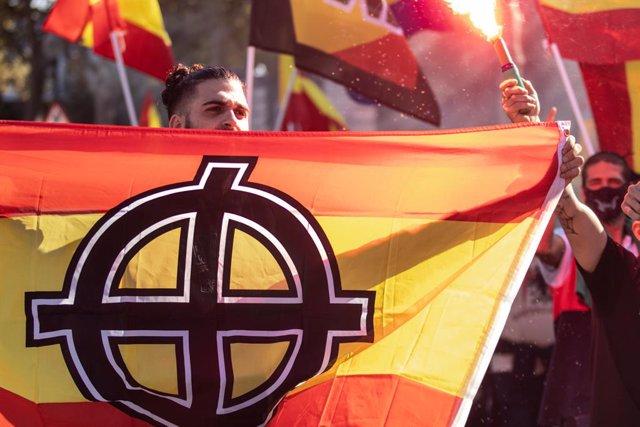 Arxiu - Un jove porta la bandera d'Espanya amb un símbol nazi imprès durant una manifestació neonazi el dia de la Hispanitat