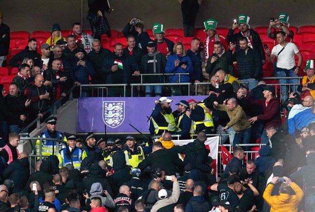 12 October 2021, United Kingdom, London: Hungary fans clash with police officers in the stands during the 2022 FIFA World Cup European Qualification Group I soccer match between England and Hungary at Wembley Stadium. Photo: Nick Potts/PA Wire/dpa