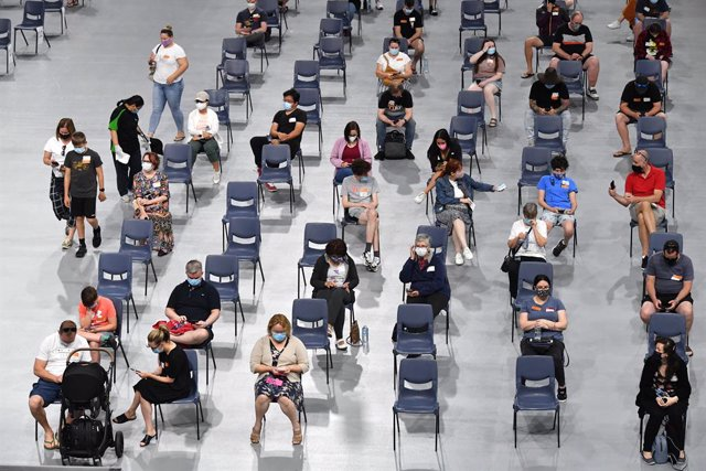 People are seen in the post vaccination observation area after receiving their COVID-19 vaccination at the Boondall mass vaccination hub in Brisbane, Saturday, September 18, 2021. Queenslanders aged 12 and over are urged to make the most of a state-wide v