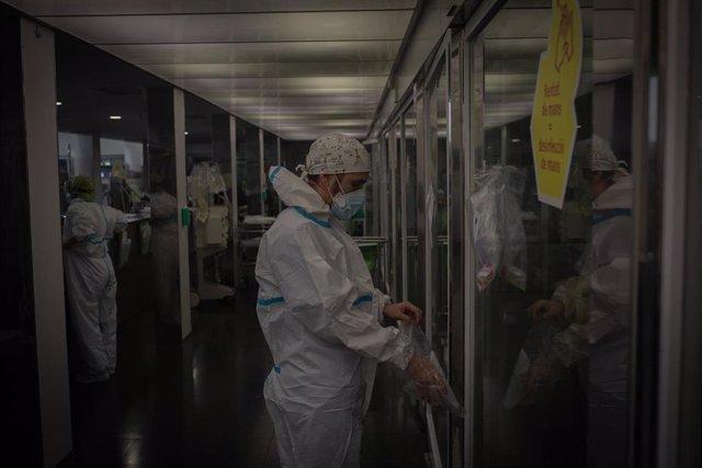 Archivo - Un trabajador sanitario protegido en una UCI (Archivo)