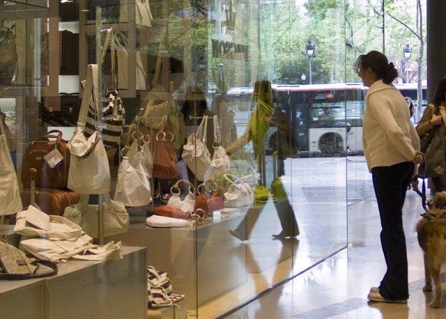 Una persona mira l'aparador d'una botiga de roba