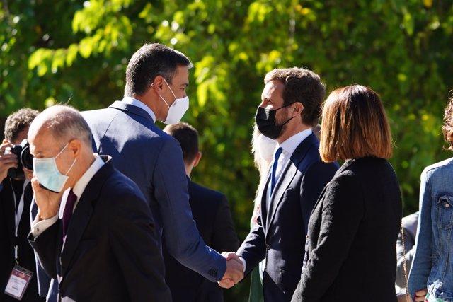 El presidente del Gobierno, Pedro Sánchez (i), saluda al presidente del Partido Popular, Pablo Casado (d), a su llegada al Real Monasterio de Yuste para asistir a la entrega de la XIV edición del 'Premio Europeo Carlos V'.