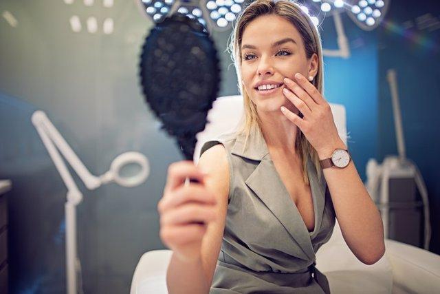 Archivo - Mujer en una clínica estética tras un tratamiento de belleza mirándose en un espejo. Botox
