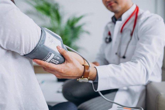 Archivo - Un doctor toma la tensión a un paciente