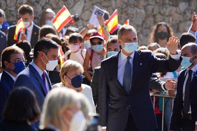 (I-D) El presidente del Gobierno, Pedro Sánchez; la canciller de la República Federal Alemana, Angela Merkel y el Rey Felipe VI, saludan al público, a su llegada al Real Monasterio de Yuste para asistir a la entrega de la XIV edición del 'Premio Europeo C