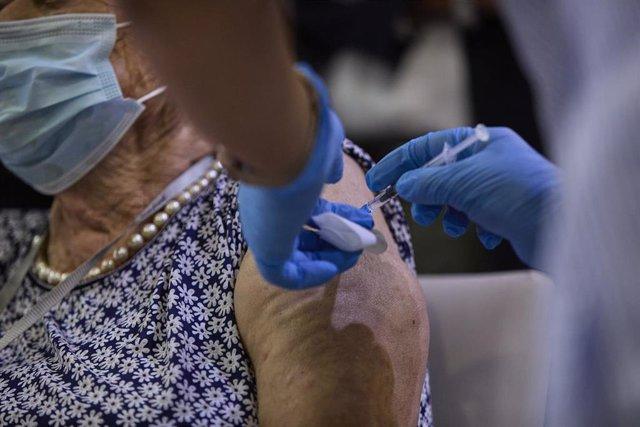 Una sanitaria vacuna a una mujer con la tercera dosis del Covid-19
