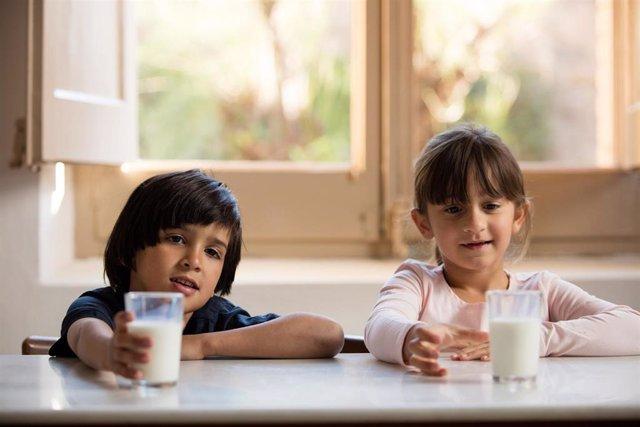 Archivo - Niños bebiendo leche.