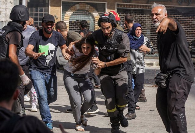 14 October 2021, Lebanon, Beirut: Civilians run for cover after gunfire erupted at a protest by supporters of the Shiite Hezbollah movement against the judge investigating the city's port port blast, near the former civil war front-line between Muslim Shi
